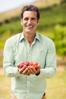 Vigneron souriant tenant des raisins