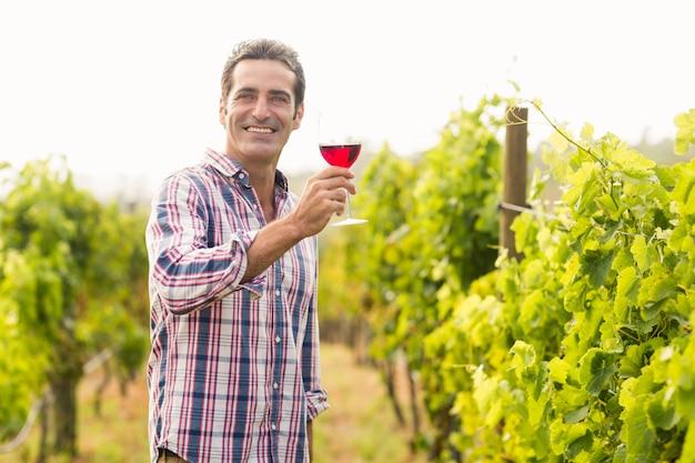Vigneron souriant tenant un verre de vin