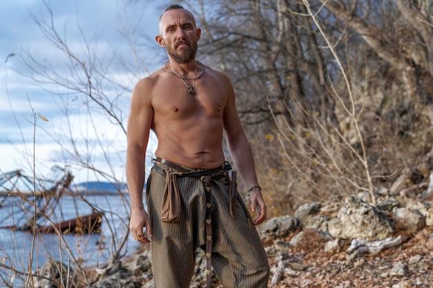 Un viking barbu se dresse sur les rives de la rivière parmi les pierres et les arbres