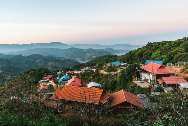 Village au milieu de couches de montagnes avec soleil et brouillard le soir