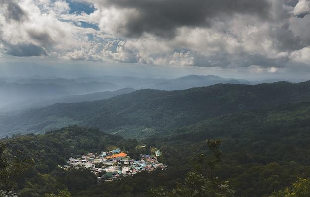 Le village au sommet de la montagne avec un ciel nuageux et un faible éclairage.