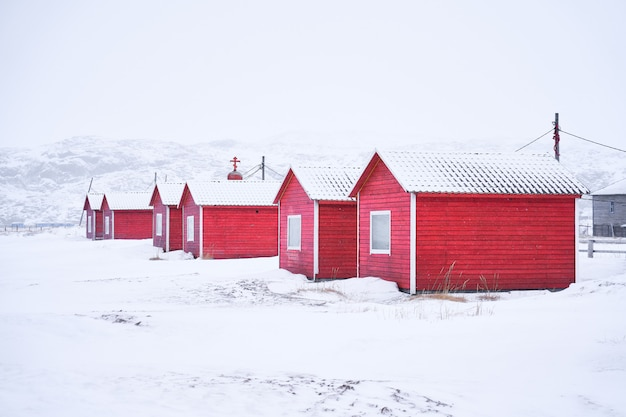 Village en bois rouge dans le paysage d'hiver
