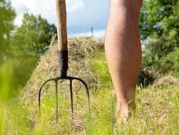 Village fourche à côté de la jambe d'un homme. à l'arrière-plan se trouve une botte de foin. notion d'agriculture. journée ensoleillée en été