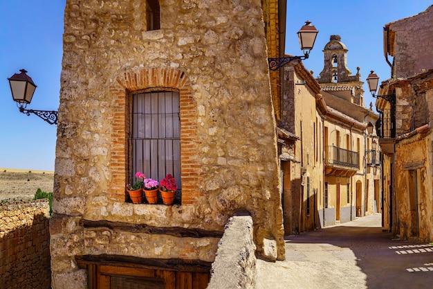 Village médiéval avec maisons en pierre, rues pavées, portes et fenêtres anciennes, arcades et murs. maderuelo segovia espagne.