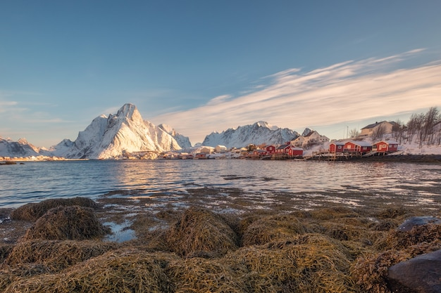 Village de pêcheurs avec montagne de neige sur le littoral
