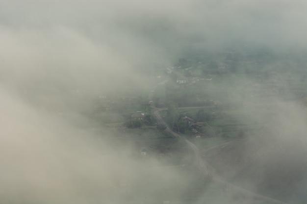 Village rustique dans les montagnes à travers le brouillard. la brume est haute dans les montagnes.