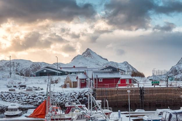 Village scandinave avec bateau de pêche et montagne enneigée sur le littoral