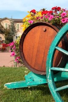 Village viticole français typique avec tonneau de vin, charrette, fleurs