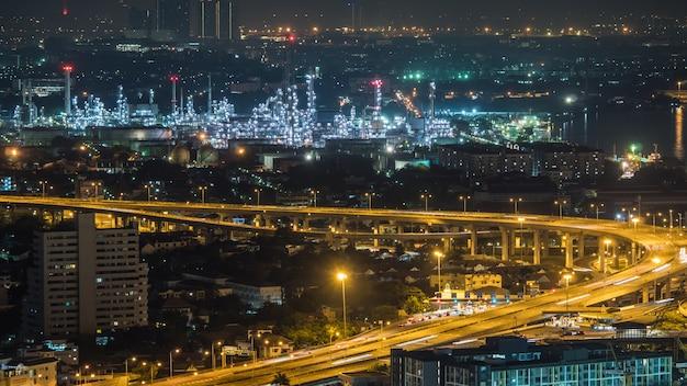 Ville de bangkok, thaïlande, montrant le trafic sur une autoroute et une raffinerie de pétrole la nuit