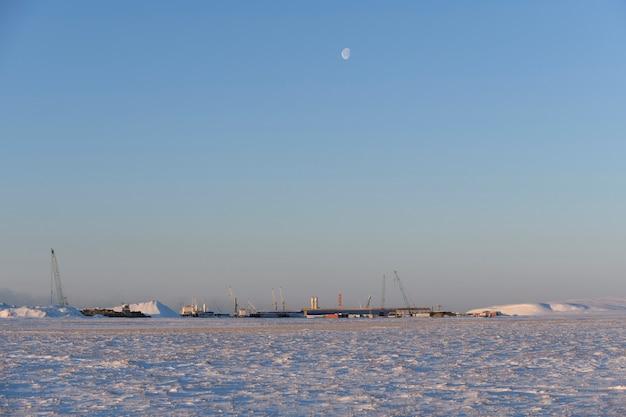 Ville dans la toundra. heure d'hiver. travaux maritimes de construction offshore.