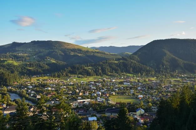 Ville dans la vallée sur fond de plusieurs montagnes boisées et ciel bleu avec des nuages