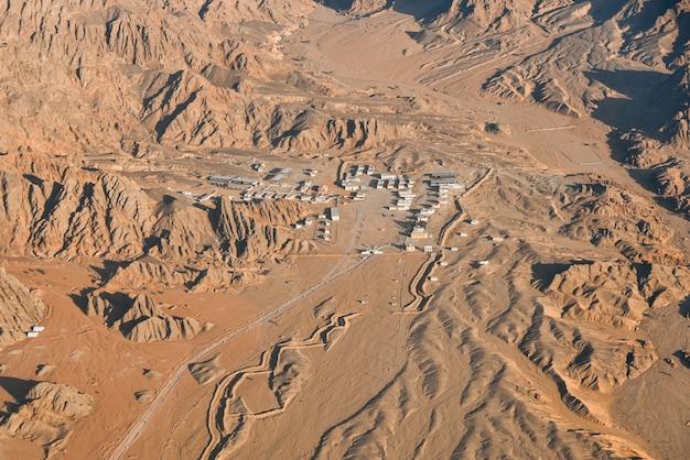 Ville déserte entre montagnes et sables, vue d'en haut