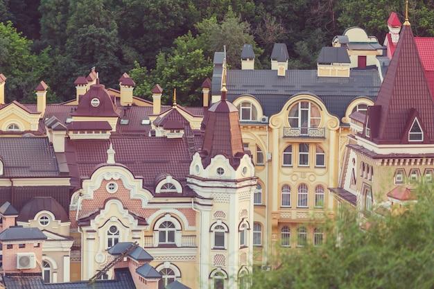 Ville de kiev. vieille ville. ukraine. belle vue sur l'ancienne rue andrew's descent et l'église saint-andré parmi les arbres verts de la colline du château à kiev