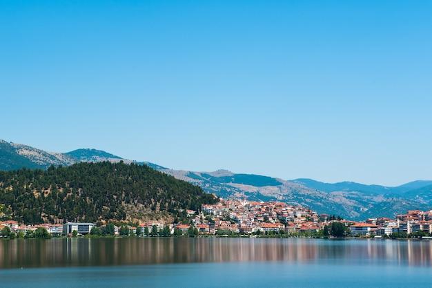 Ville sur le lac, montagnes, toits orange.