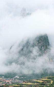 Ville et montagne rocheuse couverte de brouillard