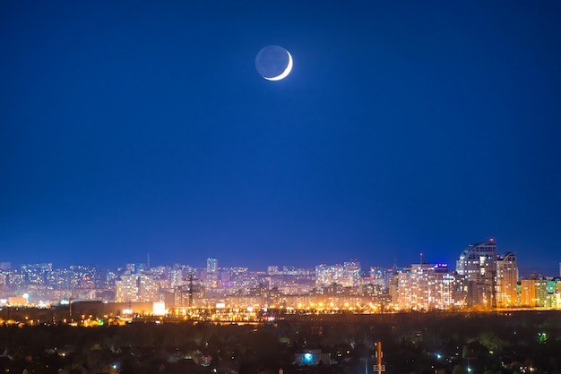 Ville la nuit avec la nouvelle lune sur un ciel bleu foncé avec des étoiles
