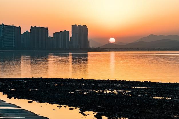 Ville et rivière au coucher de soleil