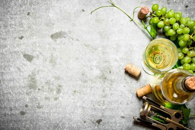 Vin blanc avec des bouchons sur table en pierre.