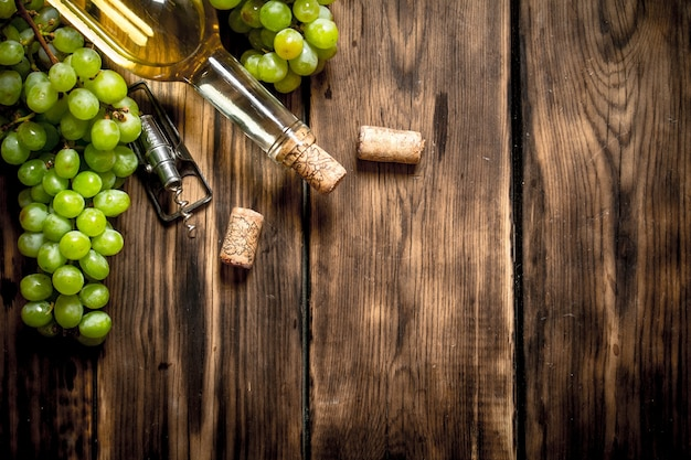 Vin blanc avec des branches de raisin blanc sur table en bois.