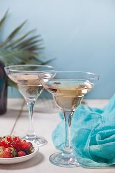 Vin blanc dans un verre, une bouteille et une assiette avec des baies.