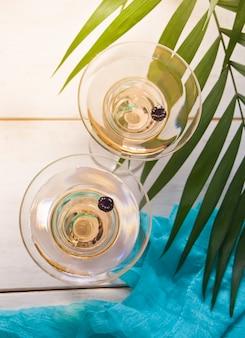 Vin blanc dans un verre sur la table en bois blanche.