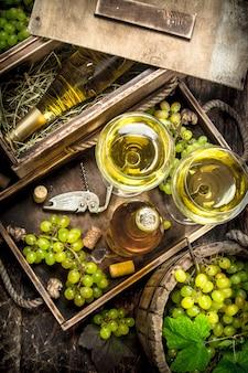 Vin blanc dans des verres sur table en bois.