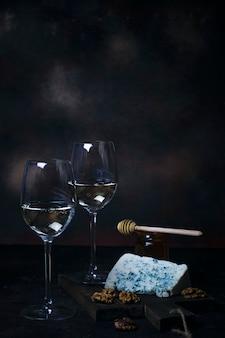 Vin blanc en verre fin avec du fromage bleu, miel, noix sur fond noir
