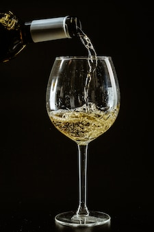 Vin blanc versé dans un verre à vin