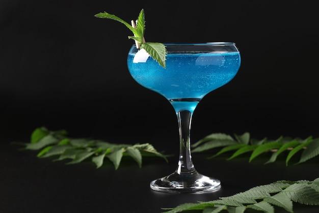 Vin bleu mousseux scintillant comestible scintillant avec garniture menthe sur fond noir