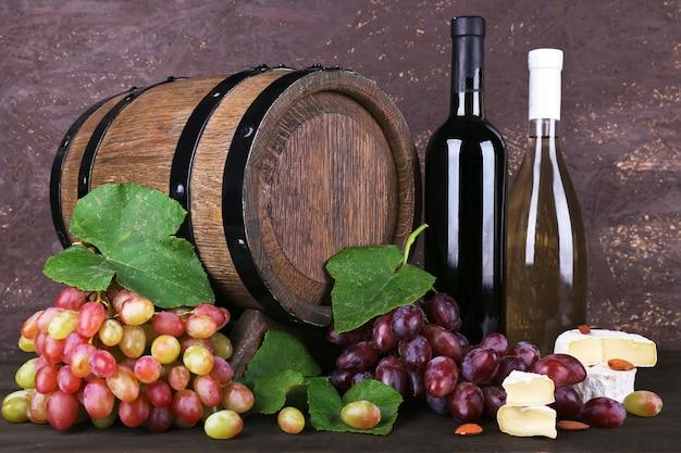 Vin en bouteilles, camembert et fromage brie, raisins et tonneau en bois sur table en bois sur fond de bois