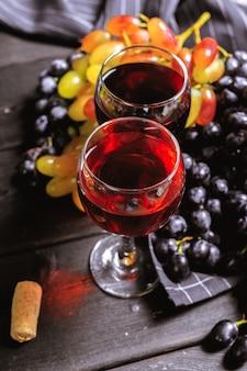 Vin avec des branches de raisins blancs. sur une table en bois