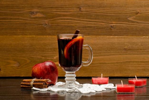 Vin chaud aux épices sur une serviette en dentelle. bougies en forme de coeur, bâtons de cannelle et pomme.