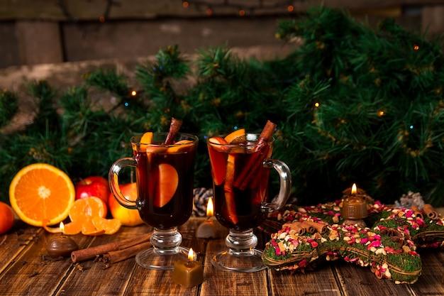 Vin chaud aux fruits et épices sur une table en bois