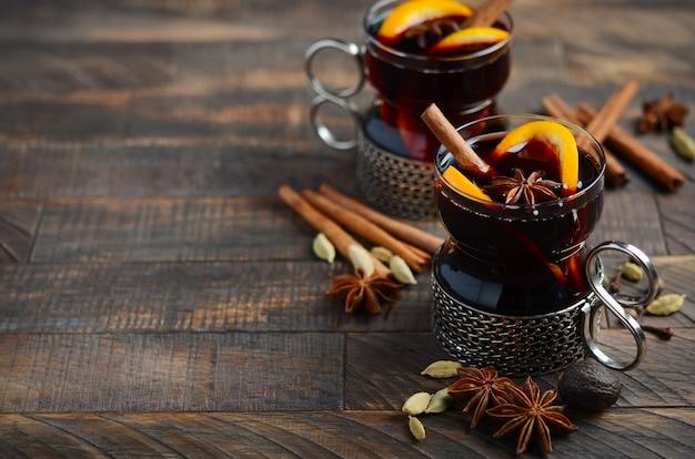 Vin chaud aux oranges et épices sur la vieille table en bois.