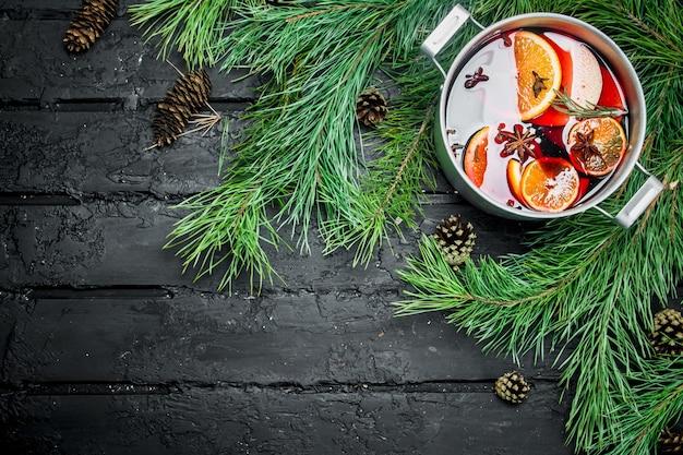 Vin chaud avec des branches de sapin et des cônes sur table rustique.