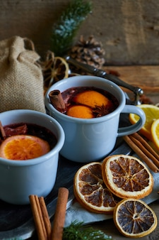 Vin chaud chaud dans des mugs gris métallisés à l'orange et aux épices de style rustique