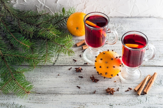 Vin chaud chaud de noël à la cannelle orange et anis sur un fond en bois blanc