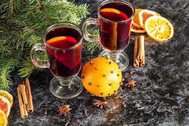Vin chaud chaud de noël avec orange cannelle et anis sur fond sombre