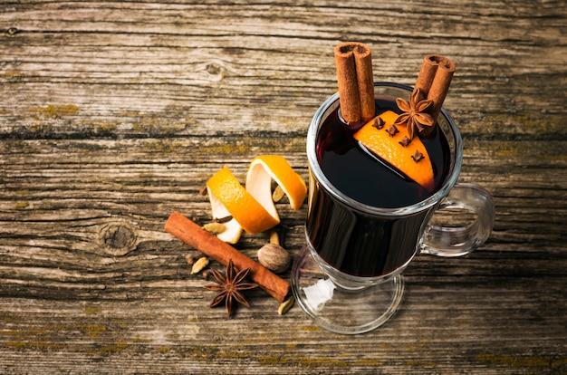 Vin chaud dans une coupe en verre sur une table en bois