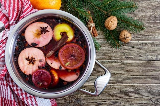 Vin chaud dans une grande casserole sur une table en bois. boisson hivernale traditionnelle parfumée à base de vin, jus, épices, assaisonnements, fruits. vue de dessus.