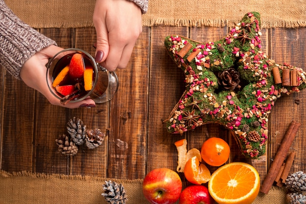Vin chaud dans les mains des femmes, les épices et les fruits sur la table en bois.
