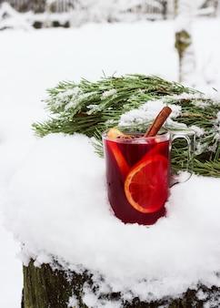 Vin chaud dans la rue dans la neige avec une branche de pin