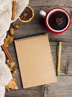 Vin chaud dans une tasse dans une caisse et un cahier