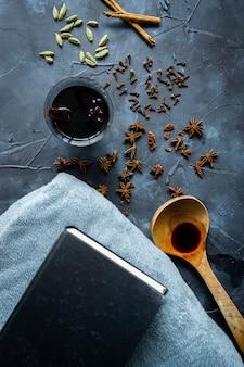 Vin chaud dans une tasse à la main, des épices, une couverture et des livres