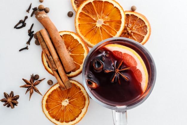 Vin chaud dans une tasse en verre, oranges séchées et épices sur fond blanc