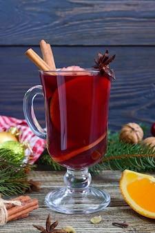Vin chaud dans une tasse en verre sur une table en bois. boisson hivernale traditionnelle parfumée à base de vin, jus, épices, assaisonnements, fruits. fermer