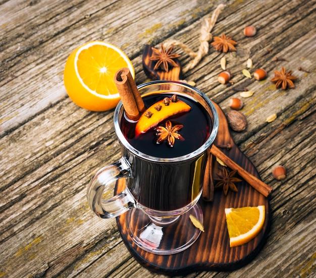 Vin chaud dans une tasse en verre sur une table en bois