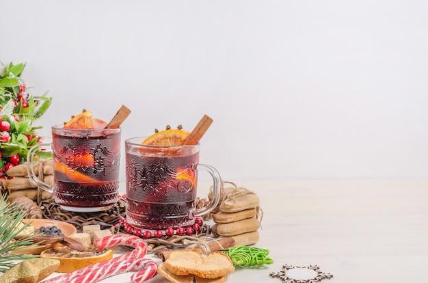 Vin chaud dans des tasses avec un décor de noël sur un fond en bois blanc avec espace copie. boisson de noël festive