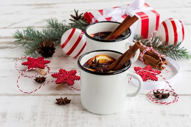 Vin chaud dans des tasses émaillées blanches avec des épices et des agrumes sur une table en bois avec des branches d'arbre à fourrure et des cadeaux de noël.