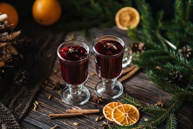 Vin chaud dans des verres avec des tranches d'orange, cannelle, clou de girofle